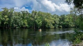 年轻夫妇人和划皮船在圣塔菲河下的妇女摄影师在一艘黄色皮船的佛罗里达有森林的 图库摄影