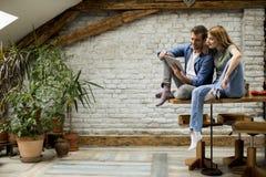 年轻夫妇使用一种数字片剂并且在厨房在家微笑着 免版税库存照片