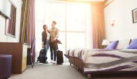 年轻夫妇到达了到蜜月的旅馆客房 免版税库存照片