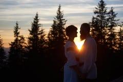年轻夫妇剪影在爱的在日落 库存照片