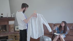 年轻夫妇包装手提箱,妇女选择一个人的衬衣 选择的概念 选择衬衣的人 股票录像