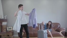年轻夫妇包装手提箱,妇女选择一个人的衬衣 高有胡子的人询问他的妻子忠告哪些 股票视频