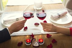 年轻夫妇吃浪漫晚餐在餐馆饮用的酒欢呼特写镜头 库存照片
