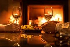 年轻夫妇吃浪漫晚餐用在壁炉背景的酒 免版税图库摄影