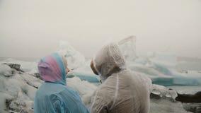 年轻夫妇后面看法在站立在冰盐水湖在冰岛和看在与灰,著名视域的冰川的雨衣的 股票录像