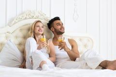年轻夫妇喝橙汁坐的床,愉快的微笑年轻西班牙人,并且妇女梦想查寻拷贝空间 免版税图库摄影