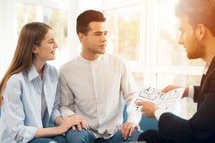 年轻夫妇在与地产商的一次会议 人和女孩做同地产商买的物产的一个合同 免版税图库摄影