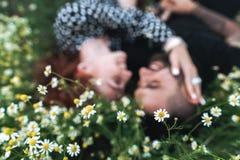 年轻夫妇在与雏菊的领域说谎 免版税图库摄影