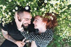 年轻夫妇在与雏菊的领域说谎 图库摄影