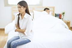 年轻夫妇在卧室,妇女单独坐并且哭泣,关系困难概念 图库摄影