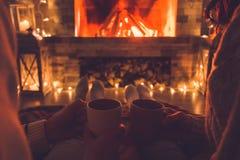 年轻夫妇在喝热的可可粉的壁炉在家冬天附近 免版税图库摄影