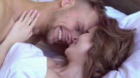 年轻夫妇在家一起圣徒华伦泰` s天概念说谎的亲吻的笑