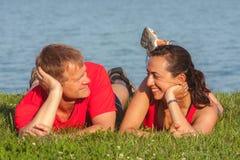 年轻夫妇在岸说谎在巴拉顿湖在匈牙利 免版税库存照片