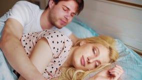 年轻夫妇在床上拥抱早晨,并且妇女张开她的眼睛 股票录像