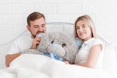 年轻夫妇在床上说谎与一个玩具熊 免版税库存图片