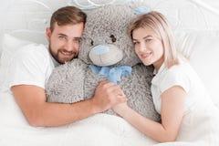 年轻夫妇在床上说谎与一个玩具熊 库存照片