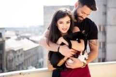 年轻夫妇在手上的拿着猫在大阳台 免版税库存图片