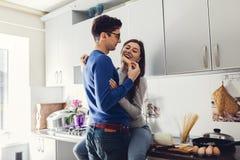 年轻夫妇在拥抱和吃乳酪的厨房里 免版税库存照片