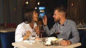 年轻夫妇在日期 一个人哺养他的妇女一个可口点心 笑在餐馆的夫妇 股票录像