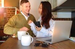 年轻夫妇在膝上型计算机附近在家喝着咖啡和笑 愉快的国际夫妇做网上购买 库存照片