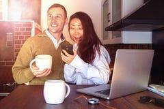 年轻夫妇在膝上型计算机附近在家喝着咖啡和笑 愉快的国际夫妇做网上购买 免版税图库摄影