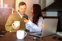 年轻夫妇在膝上型计算机附近在家喝着咖啡和笑 愉快的国际夫妇做网上购买 库存图片