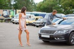 年轻夫妇在街道陈列室里选择半新车 免版税库存图片