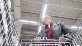 年轻夫妇在超级市场在台车买产品并且投入他们 股票视频