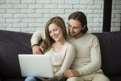 年轻夫妇坐在家拥抱使用膝上型计算机的沙发 免版税库存图片