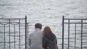 年轻夫妇坐在河赞赏的自然上的码头 免版税库存照片