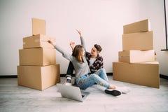 年轻夫妇坐地板满意对看在膝上型计算机的被举的手在移动新的apparment以后 在膝上型计算机的查寻ne的 免版税图库摄影