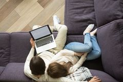 年轻夫妇坐拥抱的长沙发拿着膝上型计算机,顶视图 图库摄影