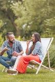年轻夫妇坐轻便折叠躺椅在绿色庭院里 免版税库存照片