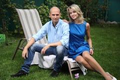年轻夫妇坐deckchair 库存照片