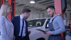 年轻夫妇客户在片剂与汽车修理店的工作者协商关于汽车维护的并且写任务在 股票录像
