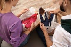 年轻夫妇打开的小包在客厅 免版税库存图片