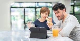 年轻夫妇挥动的手和制造视频通话 免版税库存图片