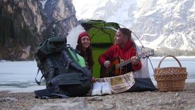 年轻夫妇旅行 坐在帐篷和唱歌由吉他在山背景  影视素材