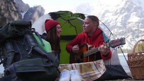 年轻夫妇旅行 坐在帐篷和唱歌由吉他 股票录像