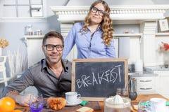年轻夫妇显示有早餐邀请的一个委员会 图库摄影