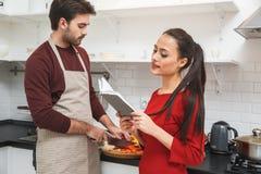 年轻夫妇有浪漫在家平衡在厨房妇女读书收据大声 免版税库存图片
