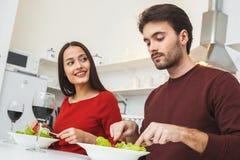 年轻夫妇有浪漫在家平衡在吃晚餐的厨房 库存照片