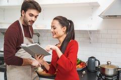 年轻夫妇有浪漫在家平衡在显示收据的厨房妇女 库存图片