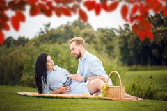 年轻夫妇有野餐在城市公园,妇女期待一个婴孩 免版税库存图片