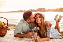年轻夫妇有野餐在海滩 人是拥抱和亲吻他的女朋友 库存照片