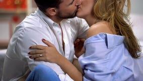 年轻夫妇热情亲吻,坐地板在卧室,统一性 库存照片