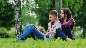 年轻夫妇男人和妇女坐草在公园,享用片剂 女孩被按反对人 股票视频