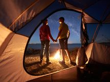 年轻夫妇男人和妇女有休息在旅游帐篷和灼烧的营火在海岸在森林附近 免版税库存照片