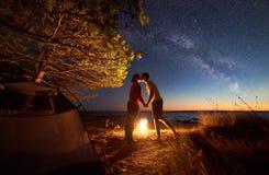 年轻夫妇男人和妇女有休息在旅游帐篷和灼烧的营火在海岸在森林附近 库存图片