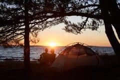 年轻夫妇男人和妇女有休息在旅游帐篷和灼烧的营火在海岸靠近森林 免版税库存照片